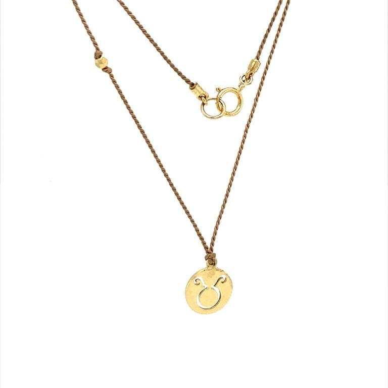 14 Karat Gold Taurus Zodiac Charm On Light Brown Silk